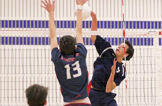 Crossroads outside hitter Aaron Lipp (right) gets a kill against Brentwood's middle blocker Shane McDonald (left) during the second set at Brentwood High School Friday night. Crossroads won the game 3-1.
