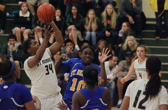 St. Monica guard Briana Harris (left) goes up for a shot against the defense of St. Bernard in the third quarter of the CIF State Playoffs at home Tuesday night.