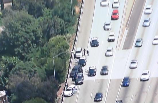 The suspects fled on foot after hitting the guardrail on the 10 Freeway near Bundy Drive.