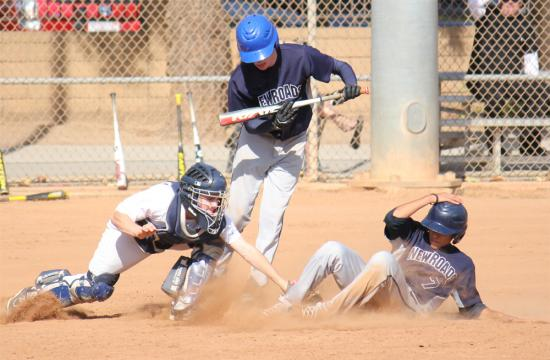 Christian Vibiano (right) of New Roads slides home to beat the tag and score a run against Wildwood in the fourth inning at Clover Park Friday afternoon.