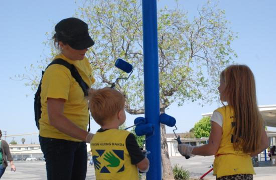 A parent and children paint a pole at Grand View Elementary on Saturday