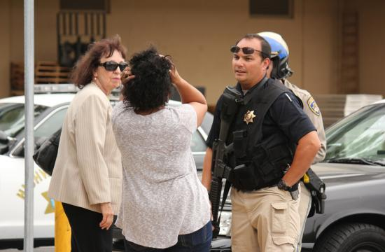 An officer talks with witnesses at Santa Monica College after a gunman shot up the school before being killed in the SMC library.