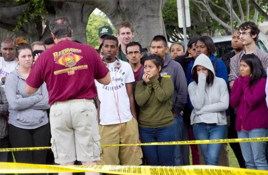 Visibly shaken Santa Monica College students listen to instructions after a shooter killed four people including one person on campus before being killed by law enforcement officials in the library Friday afternoon.