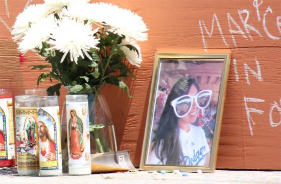 Flowers and a photo displayed against a wall at Santa Monica College for Marcela Dia Franco