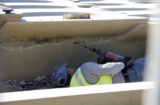 A worker is seen Tuesday jack hammering underneath a pre-cast top section of the multi-tiered fountain outside of Santa Monica City Hall. The ongoing leaks have pushed the fountain beyond its September completion date.