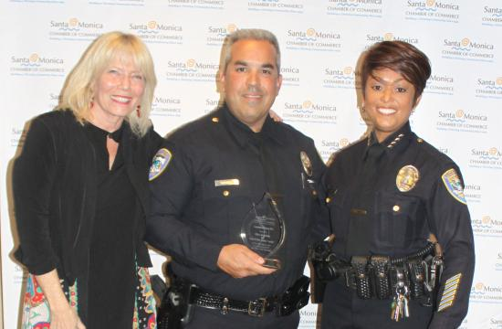 Santa Monica Chamber of Commerce president Laurel Rosen and SMPD Police Chief Jacqueline Seabrooks present Officer Adam Barry with an inspiration hero award Tuesday.