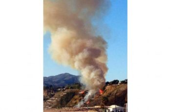 Smoke is seen rising next to the Pacific Coast Highway.