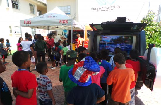 """Children at the Boys and Girls Club of Santa Monica interact with Verizon FiOS vehicles outfitted with fun electronic games and converted TVs during their """"Summer Fun Day"""" with Verizon volunteers on Friday. The initiative is part of Verizon's pledge to give back to the Southern California communities it serves."""