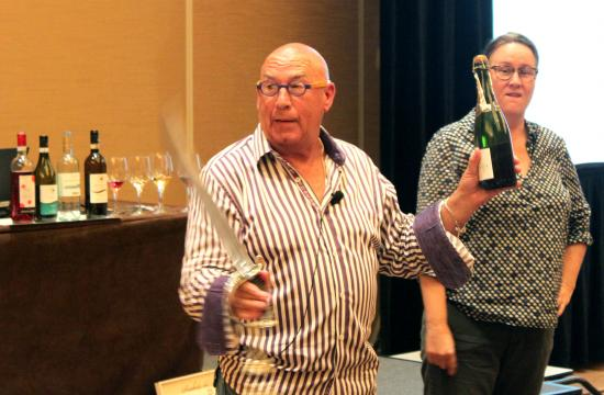 Wine expert John Cressman invites a wine seminar participant to open a bottle of wine using a sword.