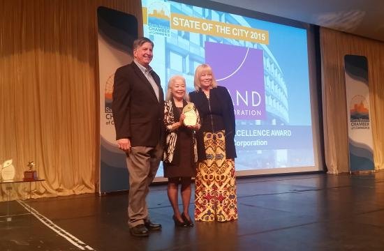 Iao Katagiri accepts the Community Excellence Award on behalf of RAND Corporation from Mayor Kevin McKeown and Chamber President Laurel Rosen at the 2015 State of the City.