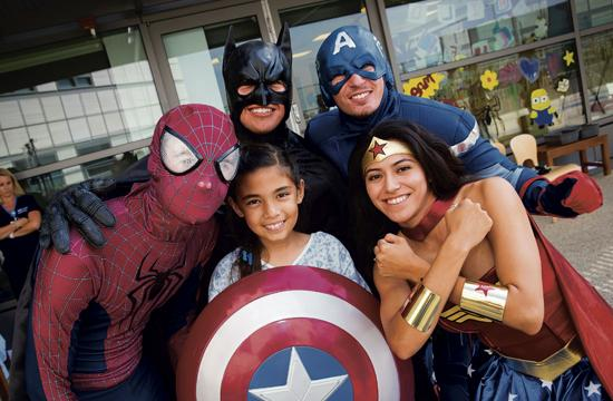 Superheroes met with children on Tuesday after they descended from the roof down from washing windows at Mattel Children's Hospital Westwood.