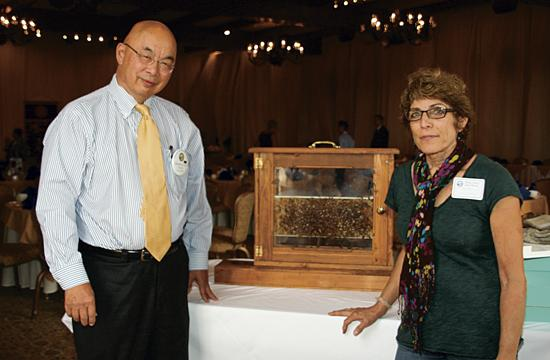 Speaker Ruth Askren and Rotary President Tom Loo with the section of a bee hive that Ruth brought with her.
