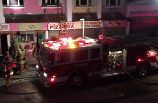 Santa Monica firefighters aided by Los Angeles firefighters battled flames Saturday night at the rear of a two-story apartment building near the Santa Monica pier.
