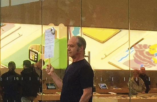 A man brandishing a flip phone protests outside the Apple store in Santa Monica Tuesday night.