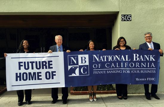 Hoisting the banner to announce the new banking office of National Bank of California at 805 Wilshire Blvd. are from left, Kathy Irby, Vice President; Dick Lawrence, Executive Vice President; Jennifer Irizarry, Vice President; Chanthan Pom, Assistant Vice President  and Operations Manager; and Rick Mateus, Regional Vice President.