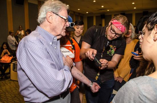 Holocaust Survivor Dr. Henry Oster shows students his identification number tattoo he received in Auschwitz