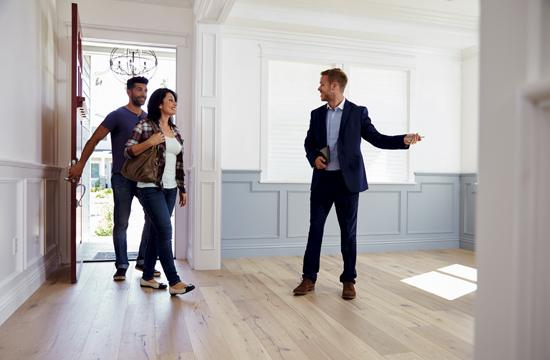Real Estate agent showing clients a home.