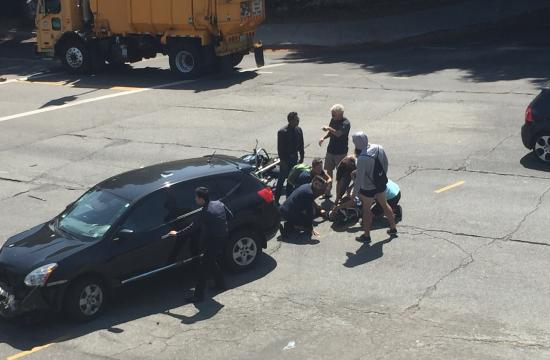 Bystanders Flock to Help Injured Motorcyclist, Who Collided With a Nissan Murano Late Tuesday Morning