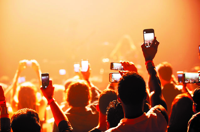 Young people filming a concert with their phones